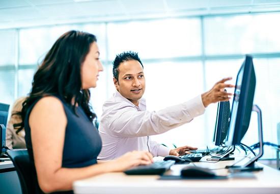 Employee providing customer training next to customer on computer